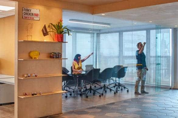 Employee using meeting room glass wall as a whiteboard