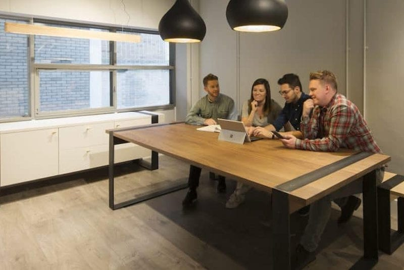 4 people sat around Haag Bench in office space