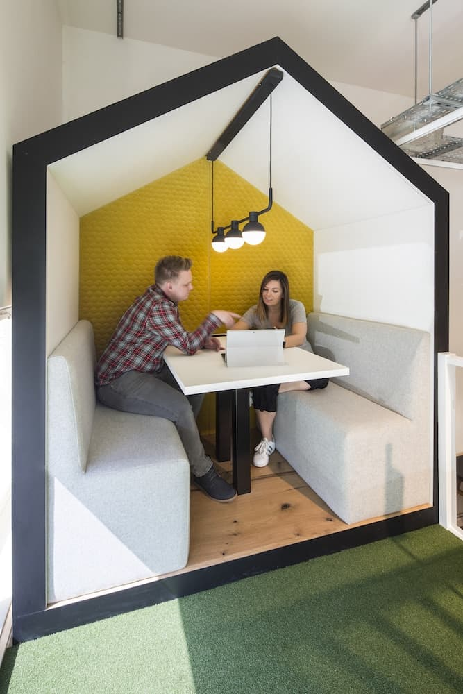 Man and woman talking in Pitched Roof Shack booth